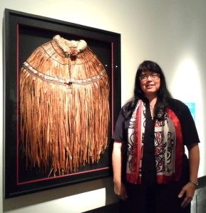 "Patti Puhn poses next to her work, Ceremonial Cape (cedar bark, sinew, abalone shell buttons, rabbit fur), winner of the 2012 In the Spirit ""Honoring the Ancestors"" award."