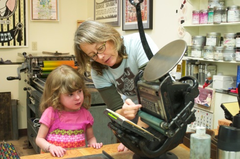 Jessica Spring shows a young visitor how the press works.
