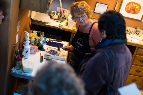 Dorothy McCuistion guides a printing demonstration with studio visitors during the Tacoma Studio Tour.