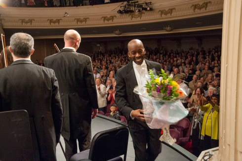 Maestro Felder exits with flowers during standing ovation.