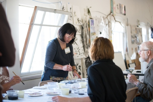 Lois Yoshida demonstrates sumi painting for visitors during the Tacoma Studio Tour.